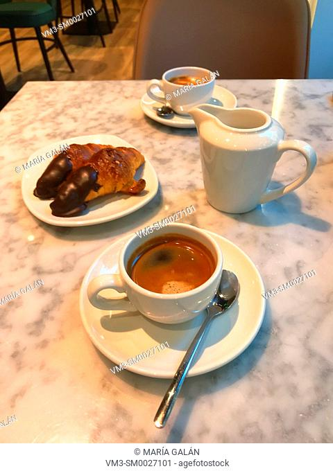 Two cups of coffee with jar of milk and two Manolitos in a cafe. Madrid, Spain
