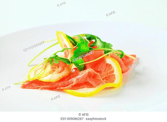 Lemon and beef carpaccio sprinkled with arugula