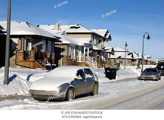 car covered in snow parked outside houses in the suburbs of Saskatoon Saskatchewan Canada