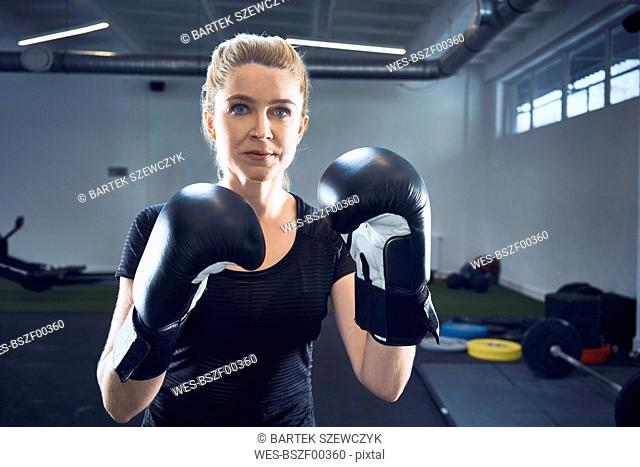Portrait of woman practicing boxing at gym