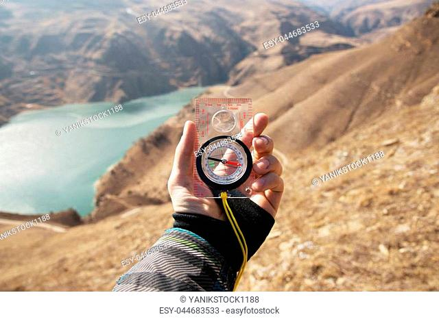 A man's hand holds a pocket magnetic compass for navigation against the backdrop of a rocky slope and a mountain lake. The concept of finding a way