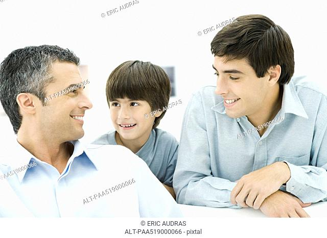 Father and two sons smiling at each other, close-up