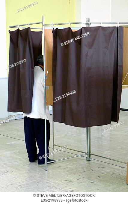 A man votes in a booth on voting day