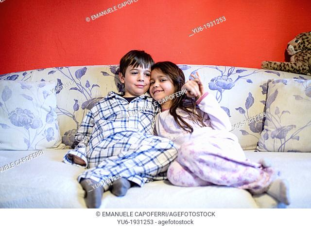 Children brothers, with his pajamas hugging each on sofa