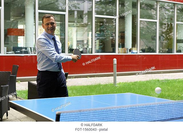 Confident happy businessman playing table tennis at creative office