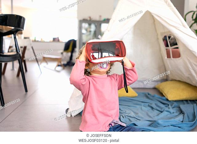 Little girl playing with VR goggles