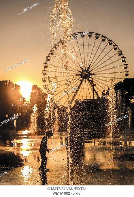 Child Playing in the Water Fountain with Ferris Wheel in Background in Sunset in Nice, France