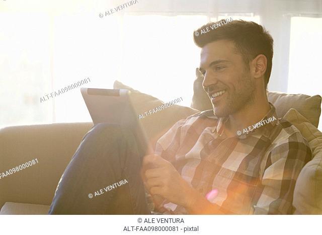 Man sitting by window, using digital tablet