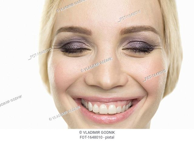 Close-up of smiling fashion model with closed eyes against white background