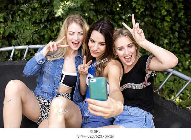Three young women photographing themselves