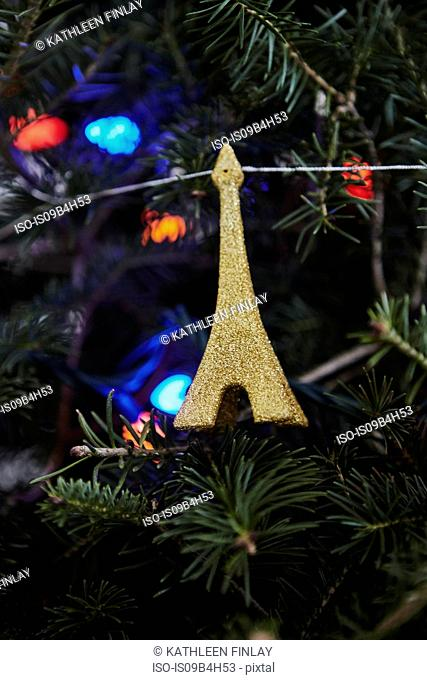 Christmas decoration, in the shape of the Eiffel Tower, hanging on Christmas tree, close-up