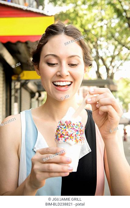 Thai woman eating ice cream in city