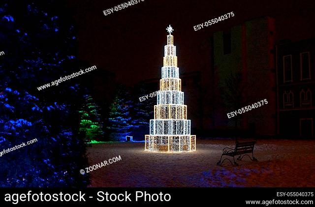 Christmas decoration of the city with electric glowing lights, Moscow avenue in St. Petersburg, Christmas tree in the yard