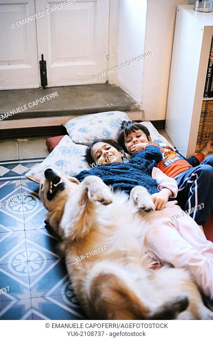 Children lying on the floor with their golden retriever dog