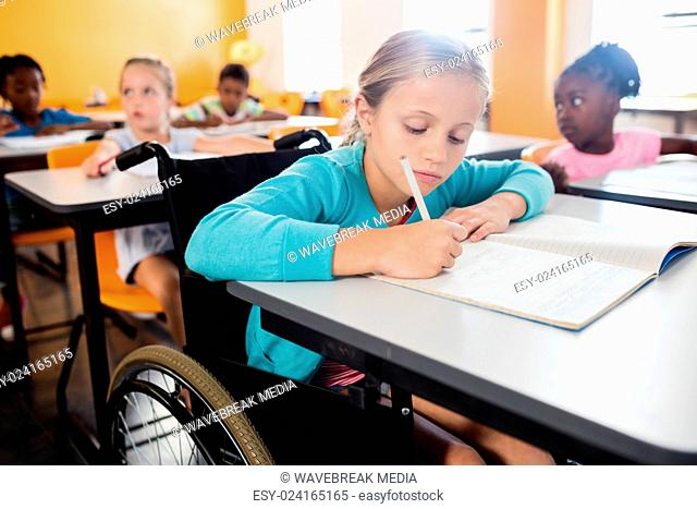 Portrait of a cute pupil in wheel chair working at desk