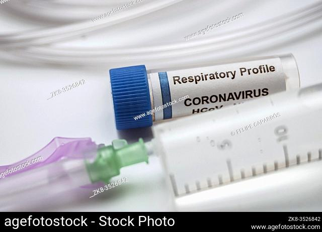 Vial with Sars-cov-2 coronavirus sample next to an oxygen mask in a hospital, conceptual image