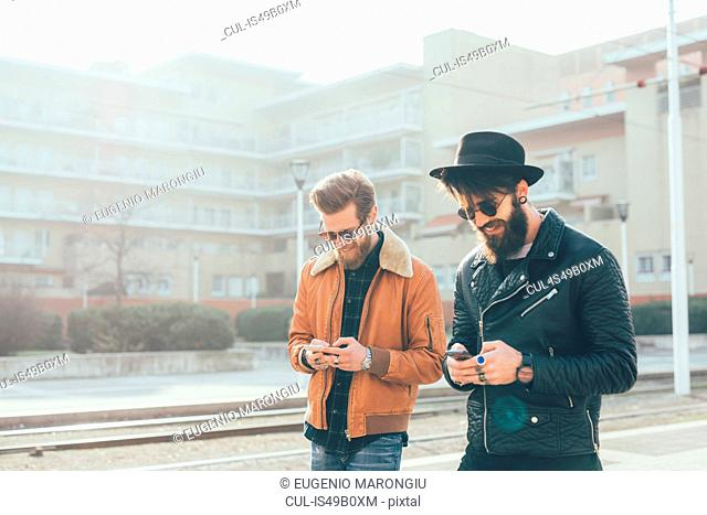 Two young male hipsters looking at smartphones at city tram station