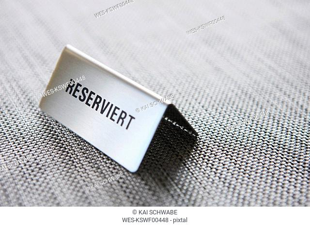 Reserved sign on grey tablecloth, close-up