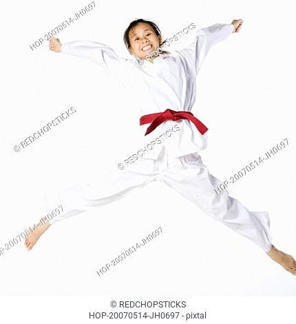 Portrait of a young woman jumping and practicing martial arts