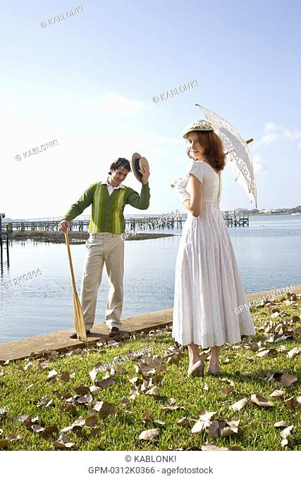 Portrait of 1920s socialite couple at garden party on water's edge, rear view