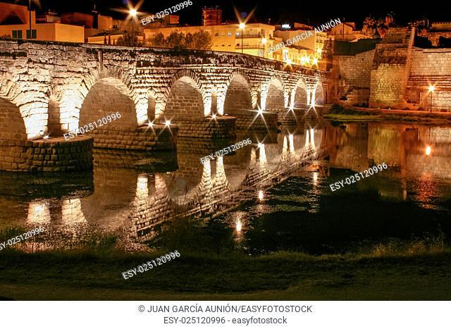 Roman bridge and alcazaba or moorish fortification at night, Merida, Spain