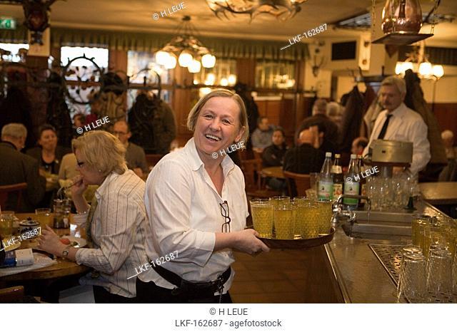 Friendly waitress serving apple cider in restaurant Zum Gemalten Haus in Sachsenhausen, Frankfurt, Hesse, Germany