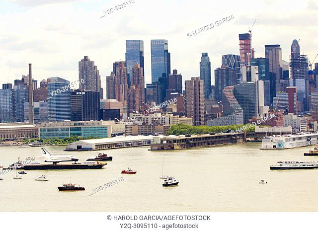 The Space Shuttle Enterprise on the Hudson River by midtown Manhattan taken to the Aircraft Carrier Intrepid where it will be placed by crane
