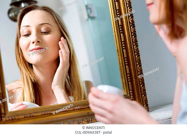 Mirror image of young woman applying face cream