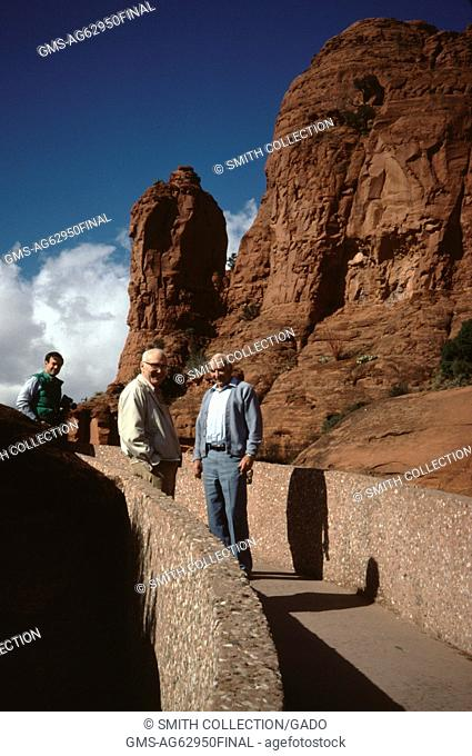Mature male tourists standing in a group on a concrete walkway leading to a red clay mesa, casting long shadows in late afternoon sunlight, Arizona, USA, 1960
