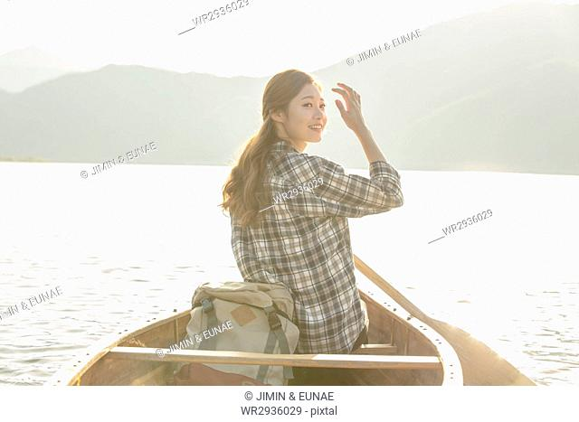 Young woman riding a canoe
