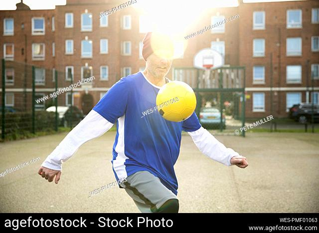 Mature man playing with football on football ground in the city