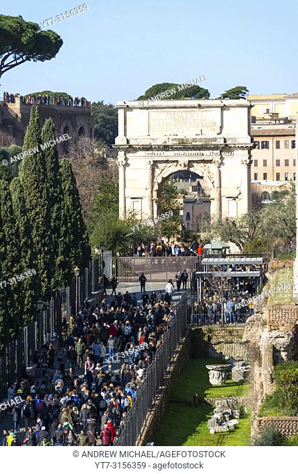Tourists queuing to enter Palatine Hill and Roman Forum, with the Arch of Constantine to the rear. Elevated view from Colosseum, Rome, Italy