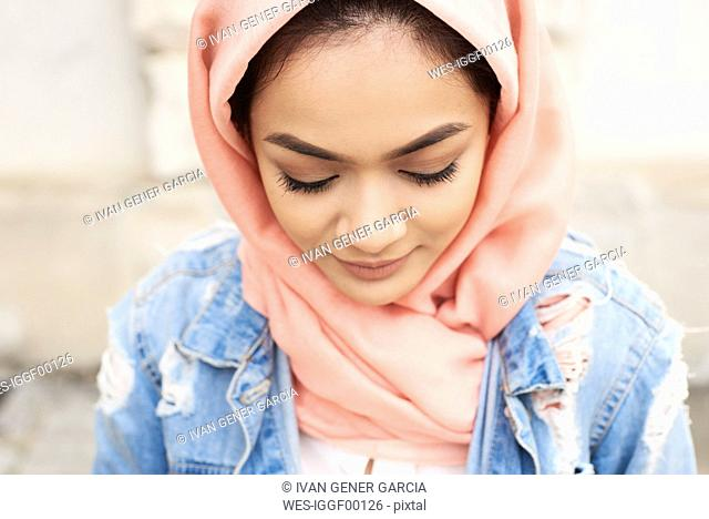 Close-up of young woman wearing hijab looking down