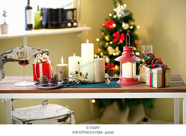 Christmas Candle, Lantern, Gift Boxes On Table In Front Of Decorative Christmas Tree