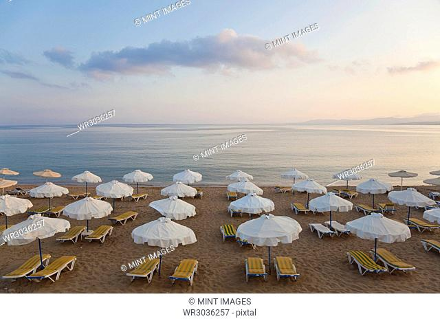 High angle view of rows of sun loungers and umbrellas on a sandy beach in the Mediterranean