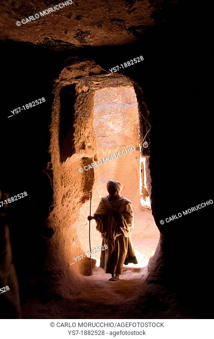 Pilgrim walking through a narrow passage to reach the entrance of Bet Amanuel monolithic rock-cut church in Lalibela, Ethiopia, Africa