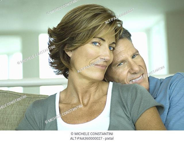 Mature couple, man resting head on woman's shoulder