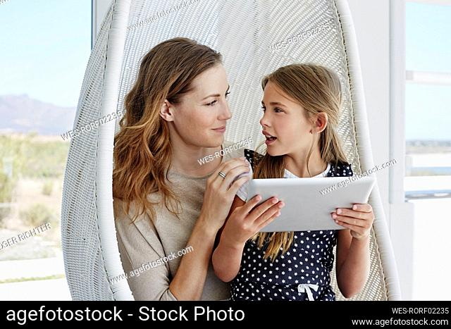 Mother and daughter sitting in hanging chair using tablet