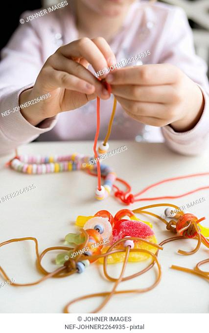 Girl making candy jewelry