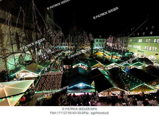 People walk over the grounds of the Christmas market in Freiburg, Germany, 27 November 2017. The season of Christmas marktes has begun about four weeks before...