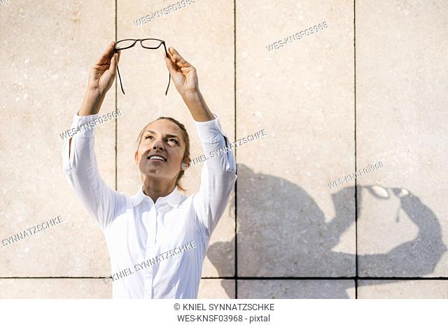 Young businesswoman looking up through her glasses