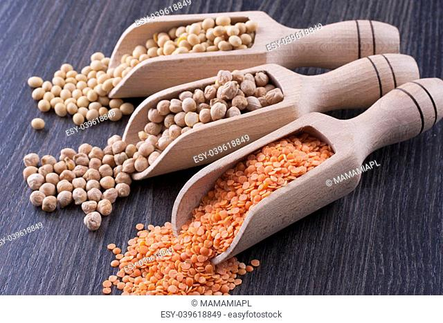 Close up photo of a raw food - orange seeds - red lentil, brown seeds - chickpeas, yellow beans - soybeans placed on a dark wooden background
