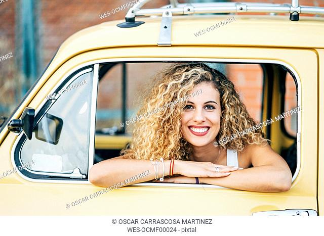 Portrait of happy blond woman looking out of window of classic car
