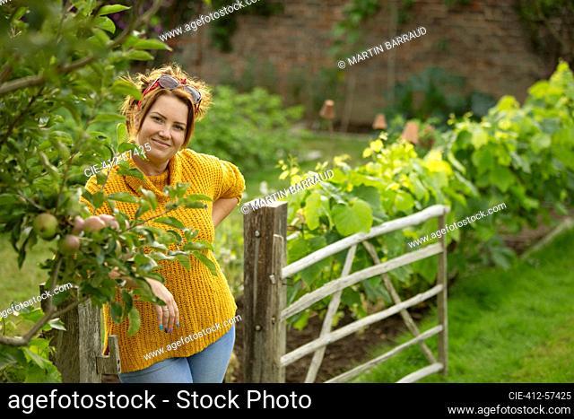 Portrait happy woman in vegetable garden