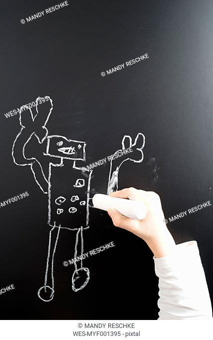 Little boy's hand drawing robot on a blackboard