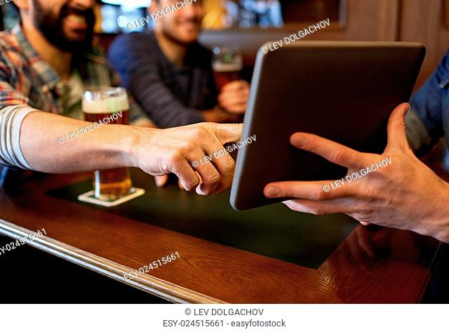 people, men, leisure, friendship and technology concept - close up of happy male friends with tablet pc computer drinking beer at bar or pub