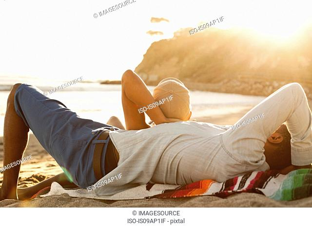 Young couple lying together on beach, rear view