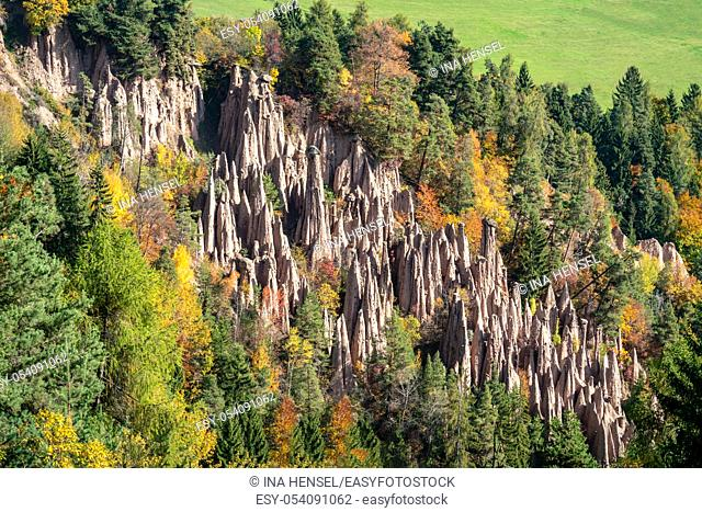 Detailed picture of the famous earth pyramids near Ritten in South Tyrol on a sunny autumn day with multi coloured foliage in the background