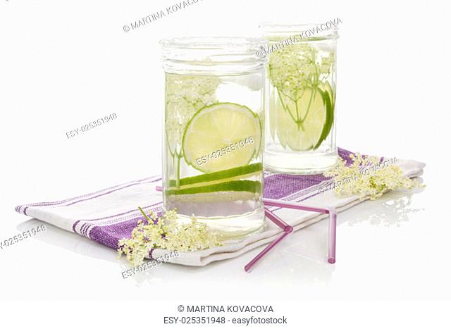 Elderberry lemonade. Two glasses with elderberry lemonade with ice and lime slices isolated on white background