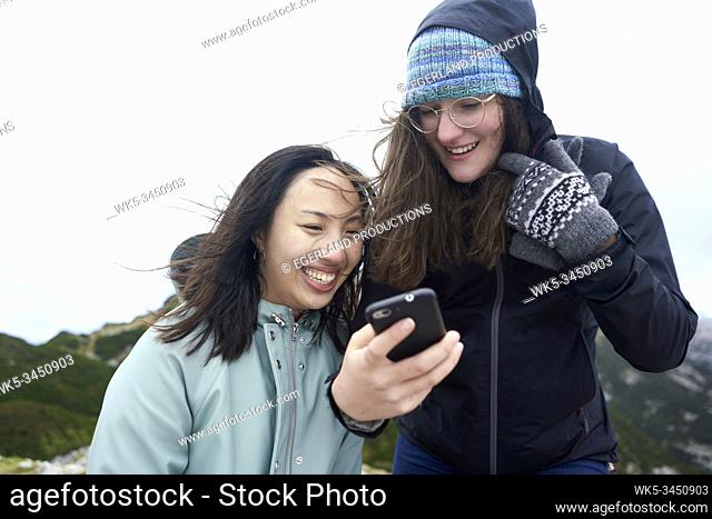 friends looking at smartphone during hiking trip
